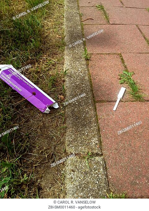 pregnancy test lying on sidewalk. Shot in Limburg province of the Netherlands