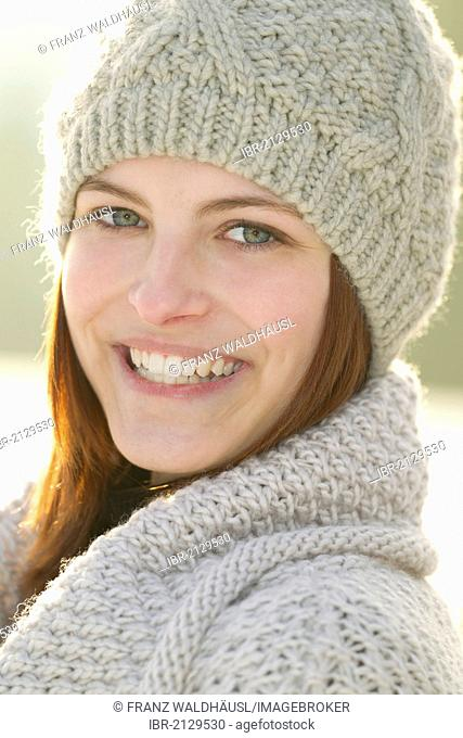 Young woman wearing a cardigan and a woolen hat