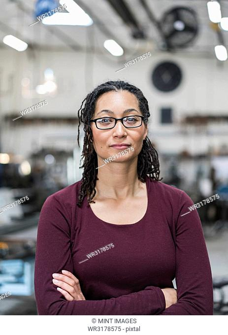 Woman with brown hair wearing glasses standing in metal workshop, smiling at camera