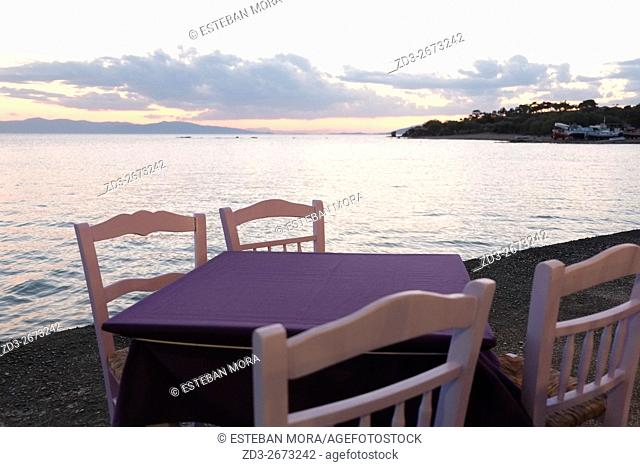 Purple table with sea views during sunset, in Aegina, Greece