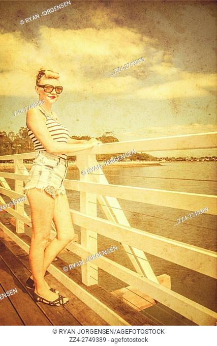 Rustic bygone photograph of a lovely 30 something pin-up beauty admiring sea sights. Faded times