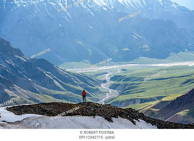 Woman exploring the rugged mountains of Kluane National Park and Reserve; Haines Junction, Yukon, Canada