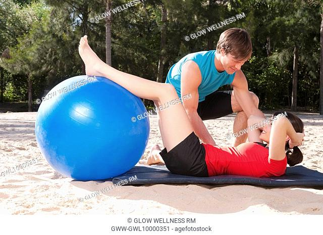 Couple exercising with a fitness ball on the beach