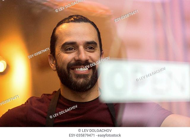 small business, people and service concept - smiling man with open word on banner at bar or restaurant window