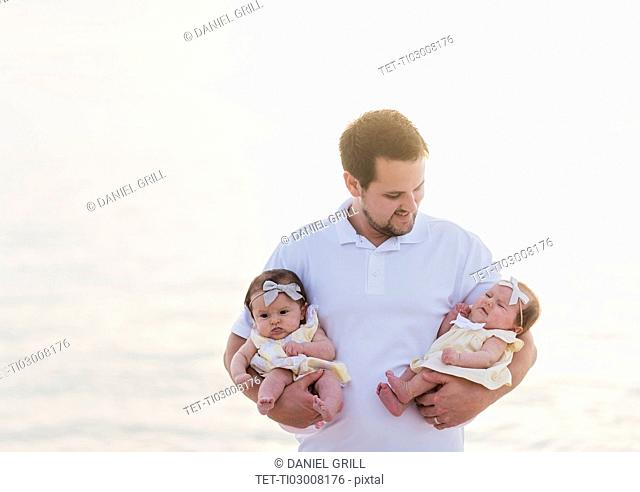 Happy father holding babies (2-5 months)