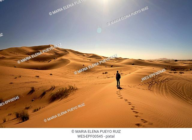 Morocco, man standing on desert dune looking at view