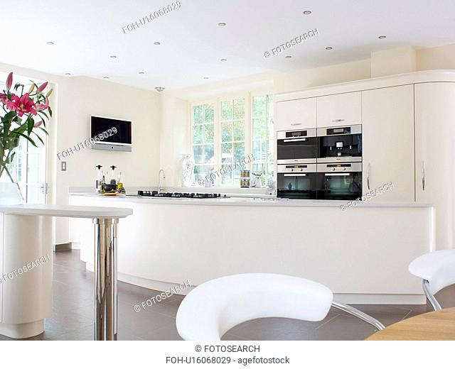 Large modern white country kitchen with curved island unit