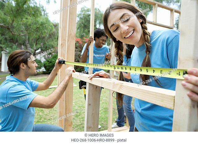 Happy volunteers measuring wooden frame at park