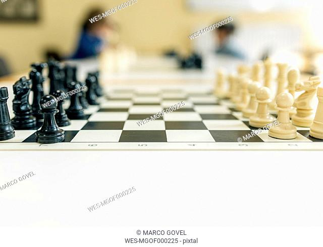 Chess game on table, children playing in background