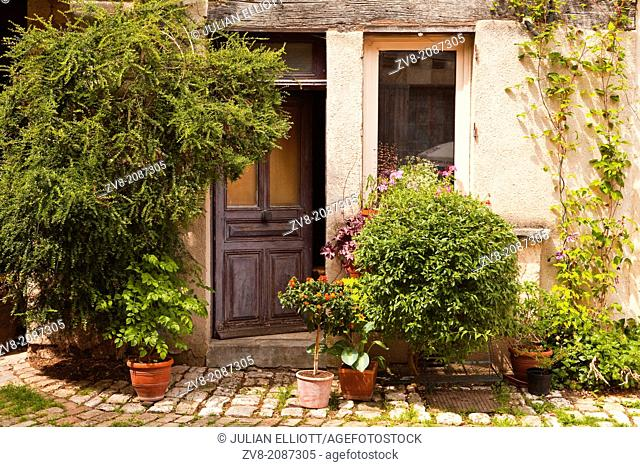 A house facade decorated with plants in the village of Noyers sur Serein