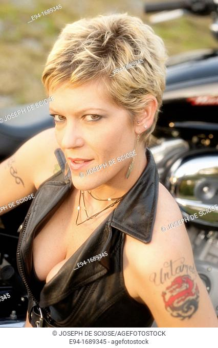 A provocative portrait of a 41 year old blond woman smiling at the camera wearing a leather vest and showing a tattoo on her left shoulder