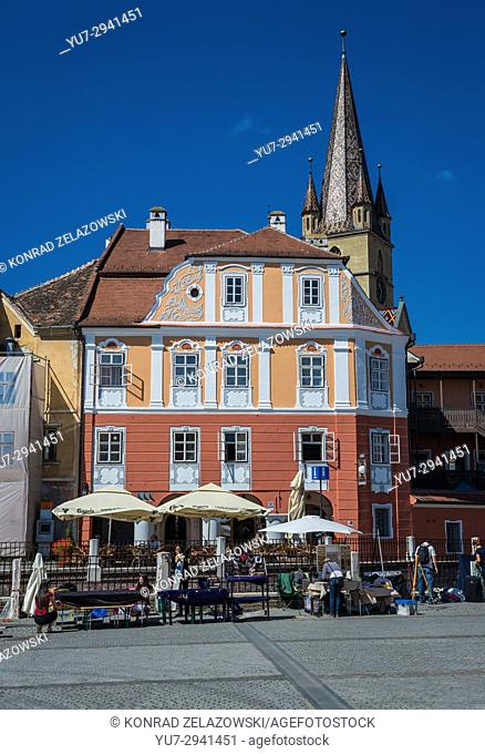 Casa Luxemburg hotel on a Small Square, Historic Center of Sibiu city of Transylvania, Romania. Bell tower of Saint Mary Cathedral on background
