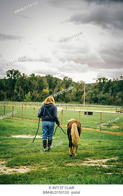 Caucasian woman walking miniature horse on ranch