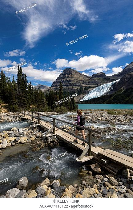 A young woman hikers over the Robson river on the Berg lake trail, with the Robson glacier and Rearguard mountain in the background, Mt