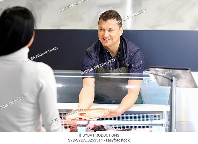 seller showing seafood to customer at fish shop
