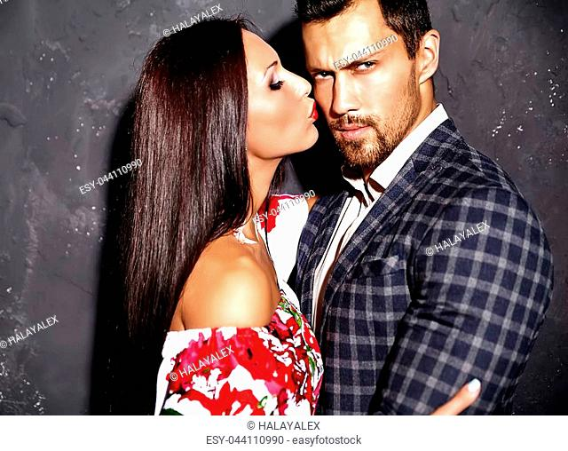 Fashion photo of handsome elegant man in suit with beautiful sexy woman kissing her man and posing near gray wall