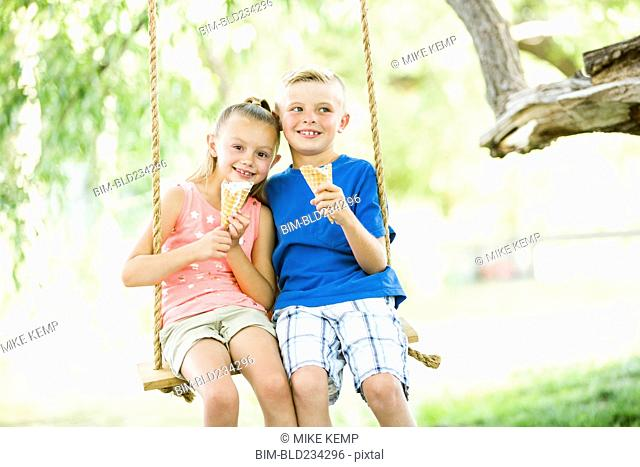 Caucasian brother and sister eating ice cream cones on rope swings