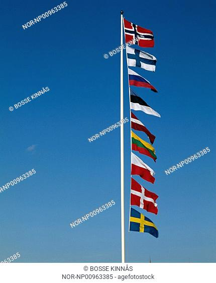 Flags waving on the flagpole in a row