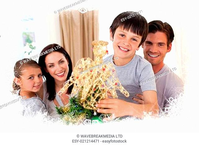 Happy little boy decorating a christmas tree with his family