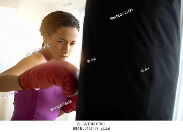 Mixed race woman hitting punching bag in gym