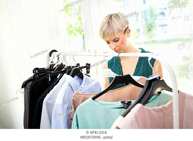 Woman choosing dress from rack against window at home
