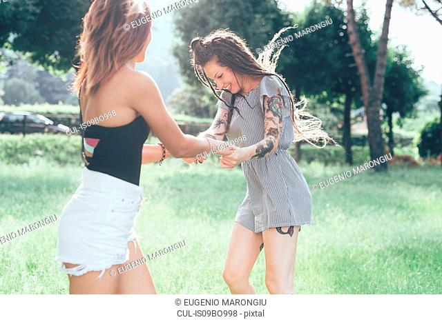 Girlfriends dancing in park