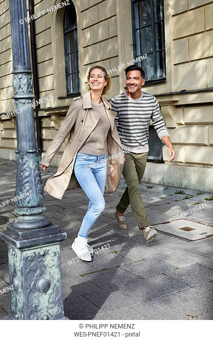 Happy couple walking on pavement in the city