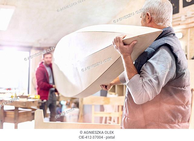 Male carpenters carrying wood boat in workshop
