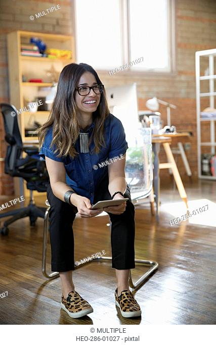 Smiling creative businesswoman holding digital tablet in office