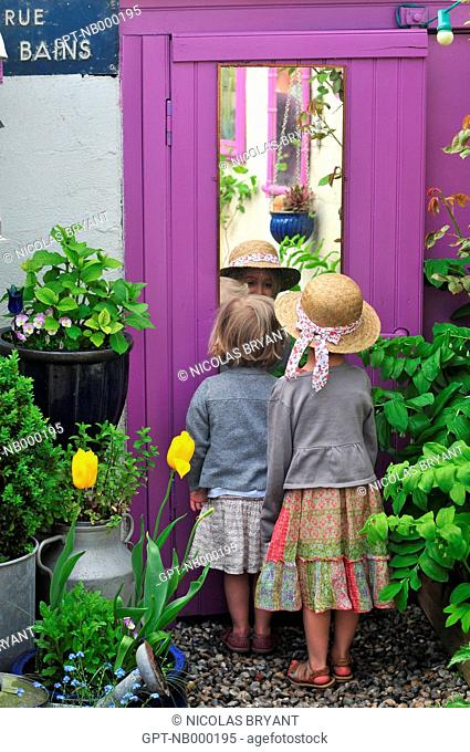 LITTLE GIRL LOOKING AT HERSELF IN A MIRROR IN THE GARDEN OF THEIR HOUSE, CAYEUX-SUR-MER, BAY OF SOMME, SOMME 80, FRANCE