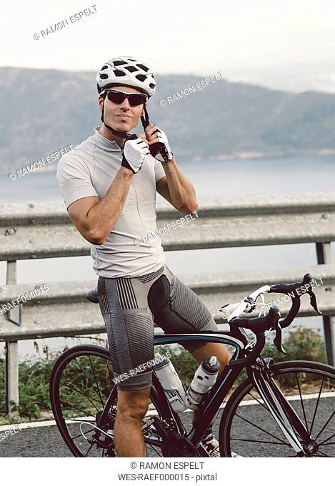 Spain, Galicia, Ferrol, male racing cyclist putting on a cycling helmet