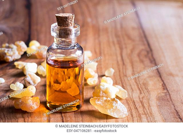 A bottle of frankincense essential oil with frankincense resin on a wooden background with copy space