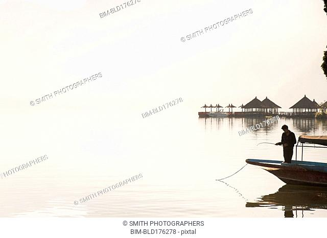 Fisherman standing in boat on still remote lake