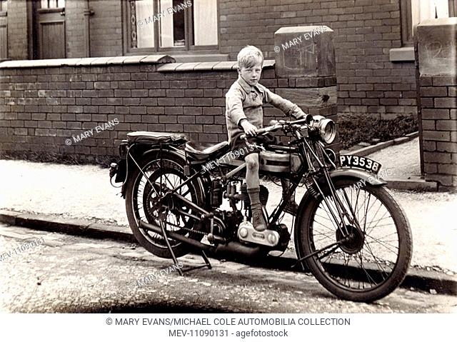 Little boy sitting on the petrol tank of a 1923/4 Triumph 350cc motorcycle in the road circa 1924