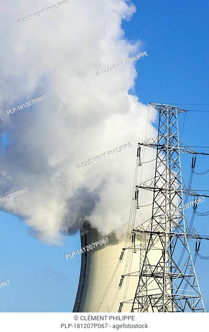 High-voltage electricity pylon / transmission tower and steam / vapour coming from cooling tower of nuclear power station / nuclear power plant