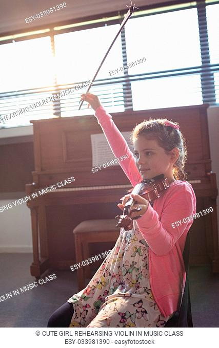 Cute girl rehearsing violin while sitting in music class