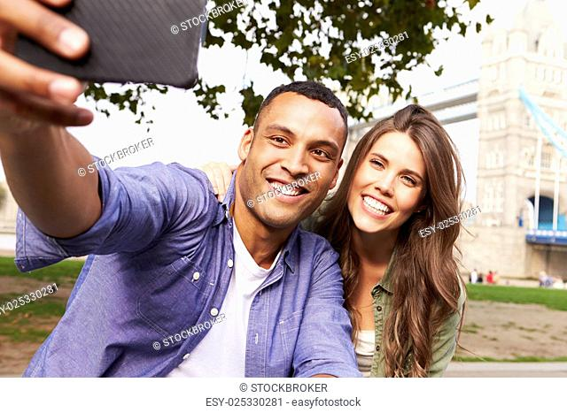 Couple Taking Selfie By Tower Bridge In London