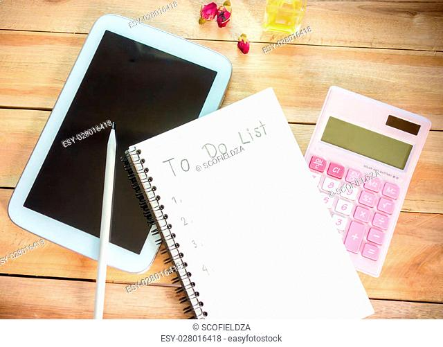 To do list notebook with tablet calculator pencil on wood floor , digital effect vintage style
