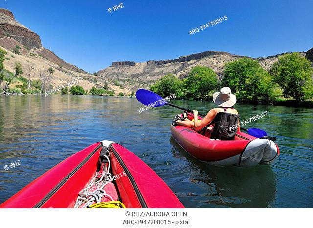 A woman in an inflatable raft on the Deschutes River in Oregon