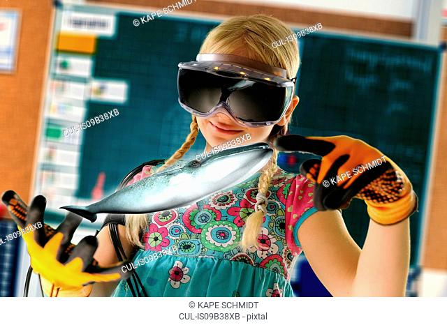 Girl pretending to be teacher wearing virtual reality headset and gloves to show whale