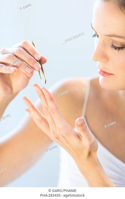 Woman removing a foreign body with a tweezer