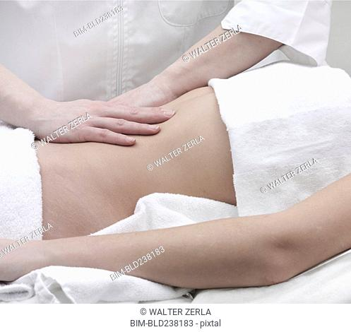 Caucasian woman receiving massage of midsection