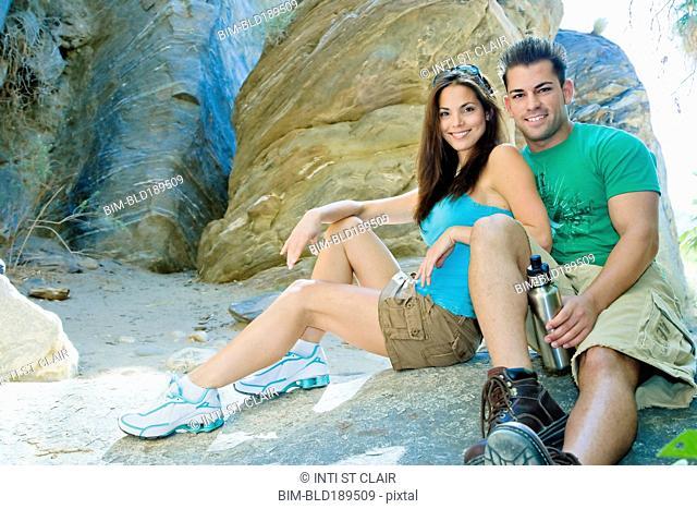 Hispanic couple sitting near rock