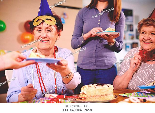 Senior women being served birthday cake at party