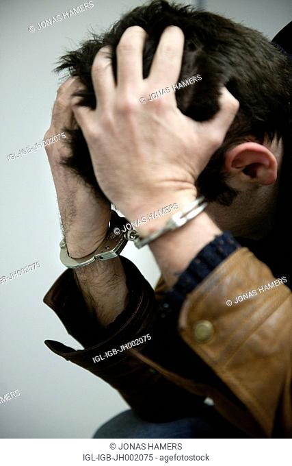 Picture shows a Handcuffed man in a police cell holding his head in his hands
