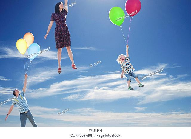 Mature couple and young son floating skyward holding onto balloons