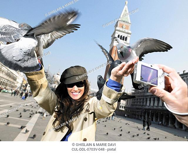 Man taking photograph of woman with pigeons St Mark's Square, Venice, Italy