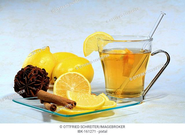 A cup of tea with lemon, cloves and cinnamon sticks on a glas plate