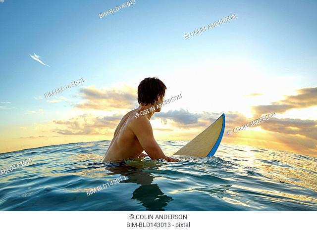 Caucasian teenage boy floating on surfboard in ocean