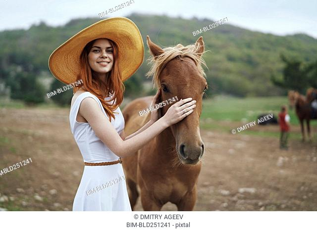 Smiling woman petting horse
